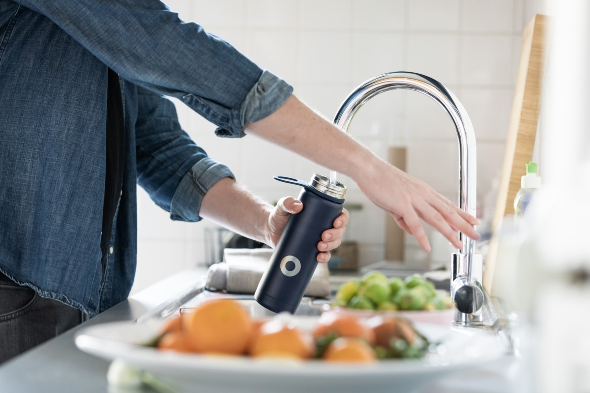 Filling a water bottle from the kitchen tap